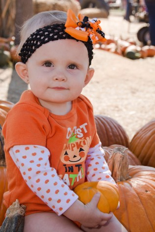Her shirt says, Cutest Pumpkin in the patch. Awh!