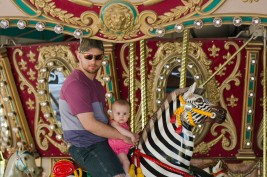 Brandon and Baby ride the carousel.