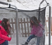 The girls play on the trampoline. Snowballs and jumping - what could be better?